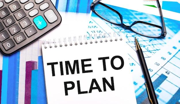 デスクトップには、色付きのテーブル、電卓、メガネ、ペン、および「計画する時間」というテキストのノートが含まれています。