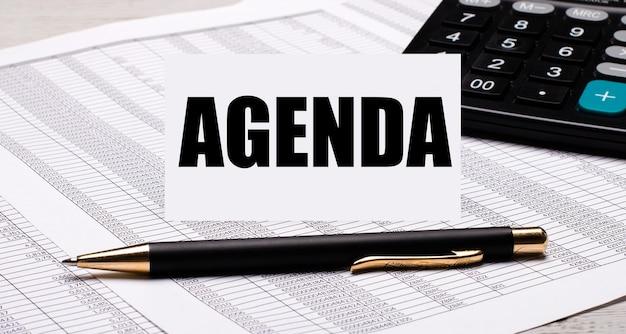 На рабочем столе находятся отчеты, калькулятор, ручка и белая карточка с текстом повестка дня.