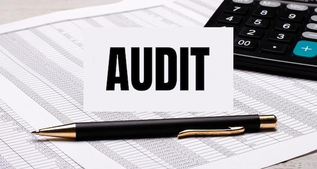 На рабочем столе находятся отчеты, калькулятор, ручка и белая карточка с текстом audit. бизнес-концепция