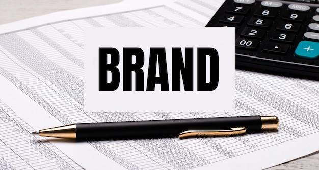 На рабочем столе находятся отчеты, калькулятор, ручка и белая карточка с текстом бренд.