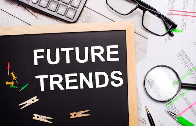 На рабочем столе есть калькулятор, отчеты, очки, лупа, ручки и доска с прищепками и текстом будущие тенденции. бизнес-концепция.