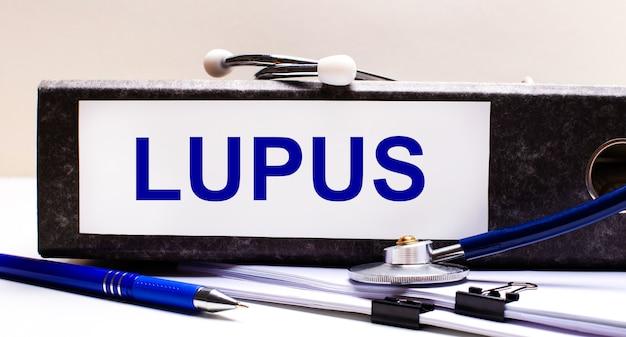 デスクトップには、聴診器、青いペン、およびテキストlupusを含む灰色のファイルフォルダーがあります。医療コンセプト