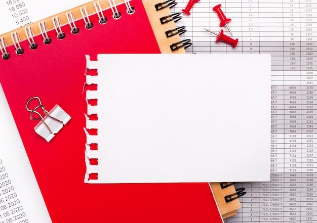На рабочем столе есть коричневые и красные блокноты, отчеты, красные кнопки и белый лист бумаги с пространством для вставки текста или иллюстраций. шаблон. бизнес-концепция