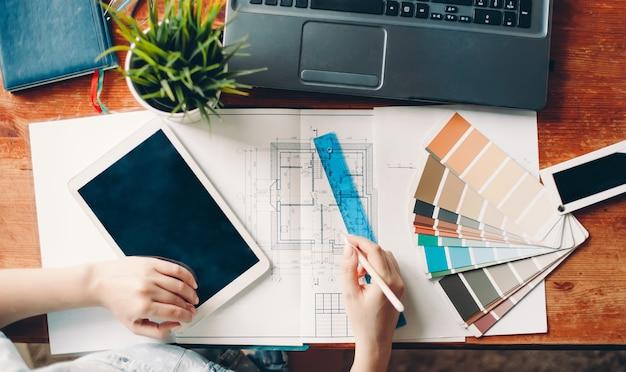 Рабочий стол дизайнера интерьера, архитектурный план дома, цветовая палитра. работа на дому