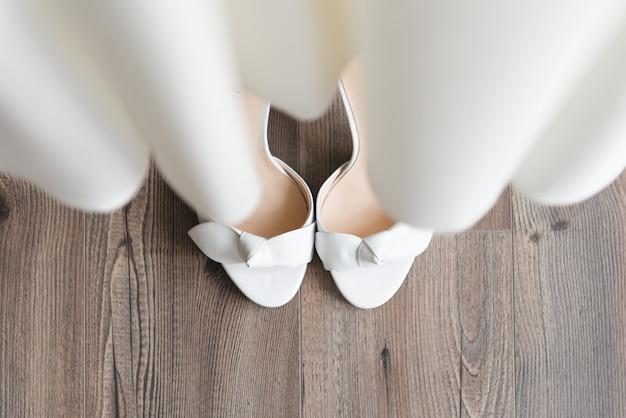 結婚式の日の詳細。明るい窓の上面に花嫁の靴