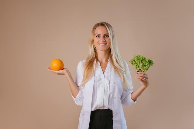 Диетолог держит фрукты и овощи