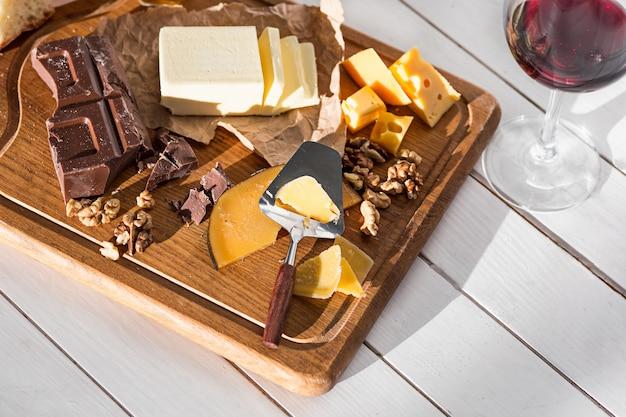 別の種類のチーズと木製の背景にクルミ