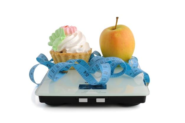 격리된 흰색 배경에 센티미터 단위로 포장된 케이크 또는 사과의 딜레마
