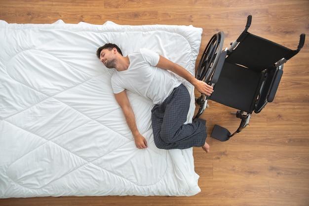 ベッドに横たわっている障害者の男性。上からの眺め