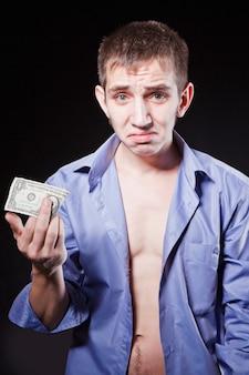 실망한 남자는 마지막 달러를 손에 들고 있다