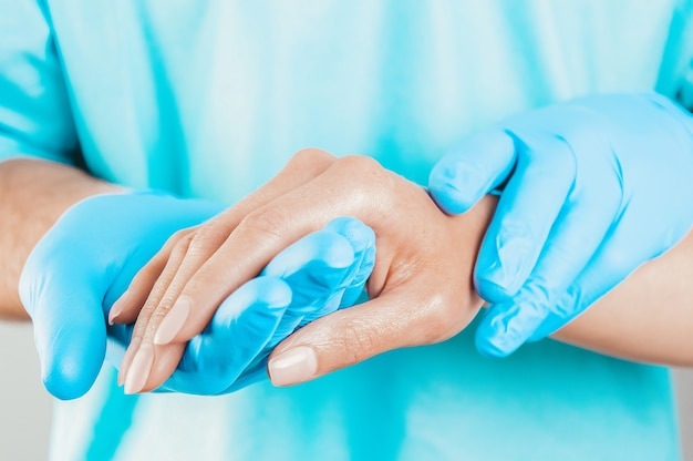 Врач бережно держит пациента за руку