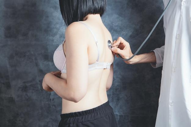 의사는 청진기로 브래지어를 입은 여성의 폐를 확인합니다.