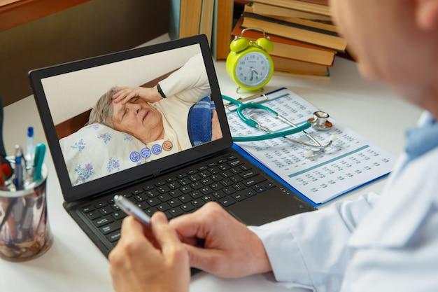 의사는 아픈 노인 여성을 상담합니다. 온라인으로 작업하십시오.