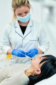 의사 미용사가 미용실에서 아름다운 여성의 입술 확대 절차를 만듭니다.