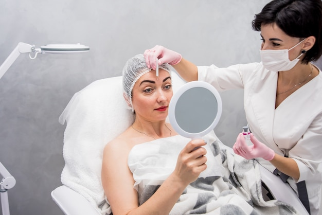 医師美容師が顔の注射手順を行います。ビューティーサロンで若い女性。