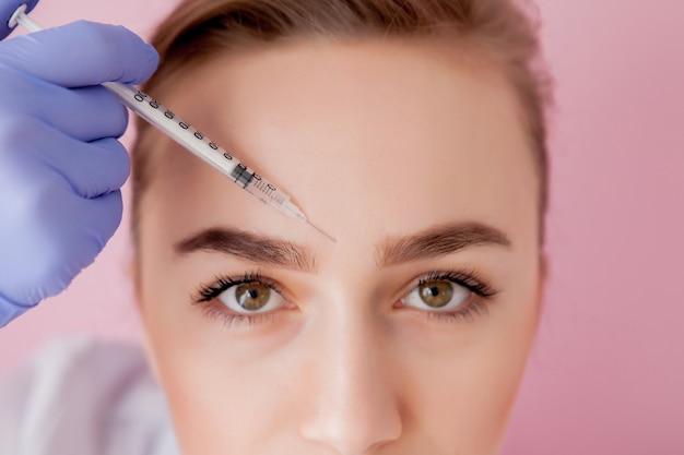 의사 미용사는 미용실에서 아름답고 젊은 여성의 얼굴 피부에 주름을 조이고 부드럽게하는 rejuvenating 얼굴 주사 절차를 만듭니다.