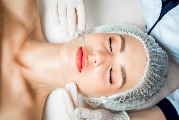 의사 미용사는 미용실에서 아름답고 젊은 여성의 얼굴 피부에 주름을 강화하고 부드럽게하기위한 회춘 얼굴 주사 절차를 만듭니다. 프리미엄 사진