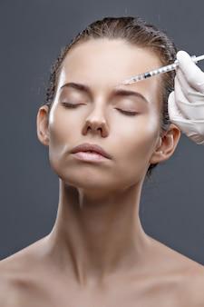 의사 미용사는 미용실 미용 피부 관리에서 여성의 얼굴 피부에 주름을 조이고 부드럽게하기 위해 젊어지게하는 얼굴 주사 절차를 만듭니다.