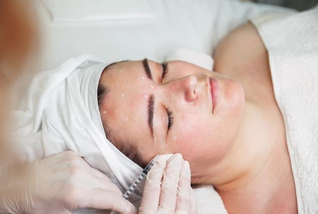 의사는 환자의 얼굴에 주사를위한 포인트를 끌어들입니다.