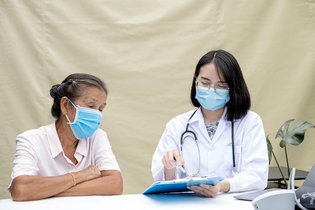 Врач объяснил результаты медицинского осмотра пожилому пациенту в полевом госпитале. они оба были в масках из-за эпидемии covid 19.