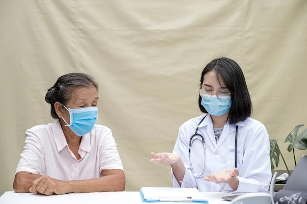 Врач объяснил результаты медицинского осмотра пожилому пациенту в полевом госпитале. они оба были в масках из-за эпидемии коронавируса.