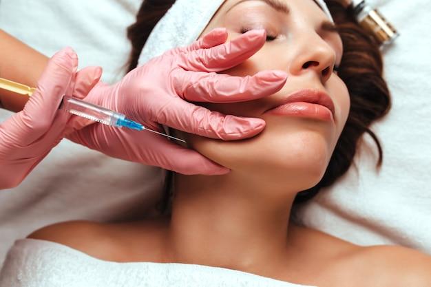 医者は女性の頬骨に注射をします