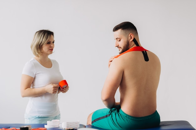 医者は特別な治療テープを男性の肘に接着します