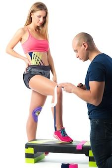 Врач приклеивает кинезиотейп к ее ноге.