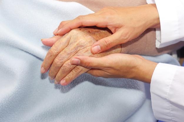 의사는 환자, 아시아 노인 또는 노인 노부인의 손을 잡고 병원이나 클리닉에서 격려합니다. 위안, 건강 관리 및 공감 개념.