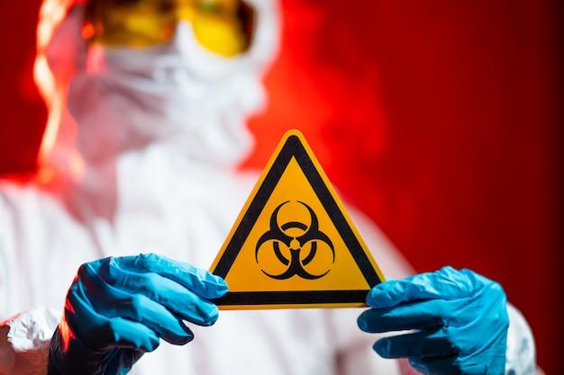 Доктор держит знак биологической опасности. страшно красный фон, карантинная зона
