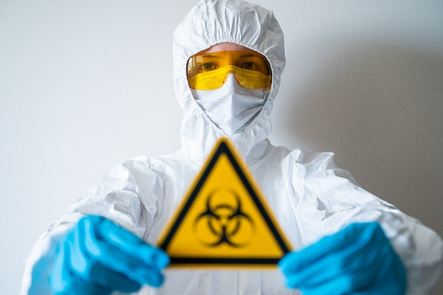 Доктор держит знак биологической опасности. карантинная зона, пандемия коронавируса