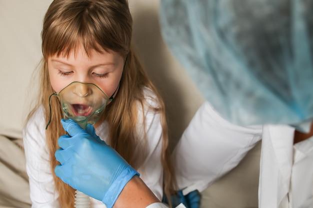의사는 아이를 위해 호흡 마스크를 들고 흡입기 산소 마스크 분무기로 호흡을 돕습니다.