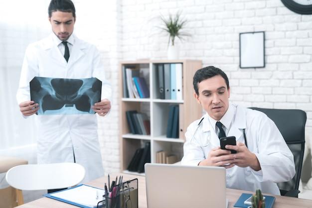 의사는 그의 손에 휴대 전화를 보유하고 있습니다.