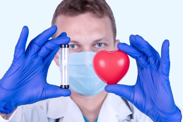医者は健康の象徴として彼の前に赤いハートを持っています