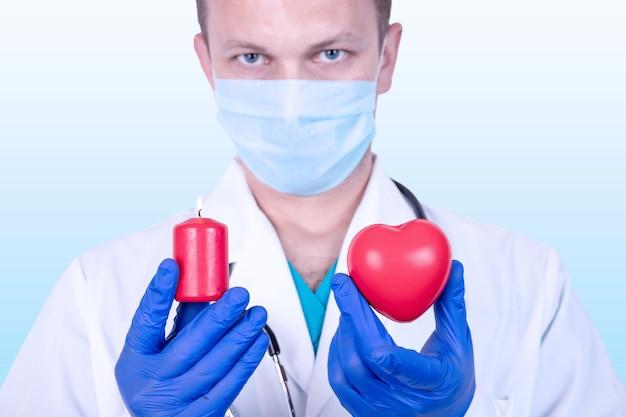 의사는 붉은 마음을 손에 들고 다른 손에는 불타는 초를 들고 있습니다.