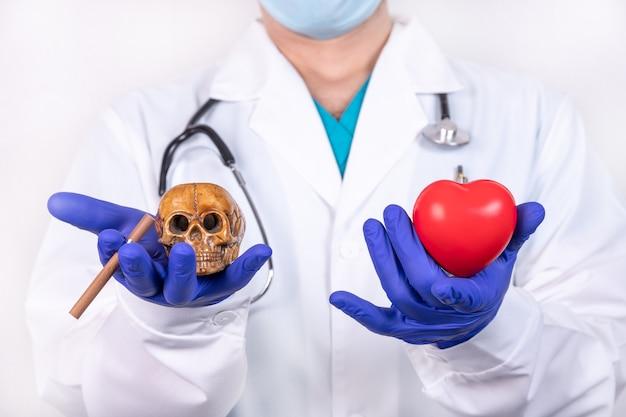 医者は片方の手に赤いハートを持ち、もう片方の手に頭蓋骨とタバコを持っています