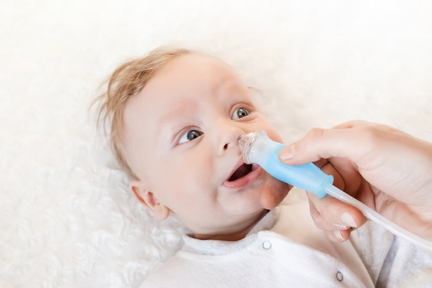 의사는 코에서 코딱지를 빨기 위해 튜브를 손에 쥐고 있습니다. 침대에는 작은 아이가 있습니다. 선택적 초점