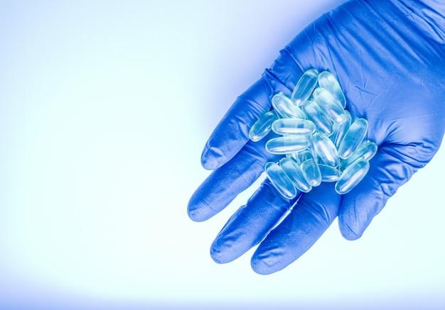医者は薬、丸薬、丸薬、オメガ3ビタミン、魚油の入ったカプセル、青い手袋をした手を持っています。病気のための薬物併用療法。青い手袋をした研究者の手にあるカプセル。