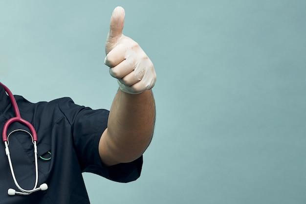 Врач протягивает руку с поднятым вверх большим пальцем