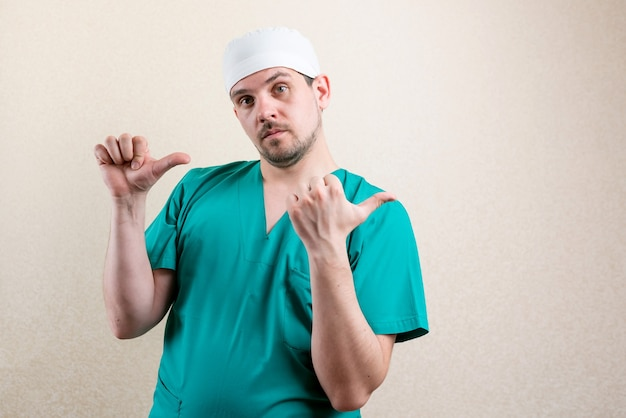 マスクと眼鏡をかけた医者が横を指しています。高品質の写真