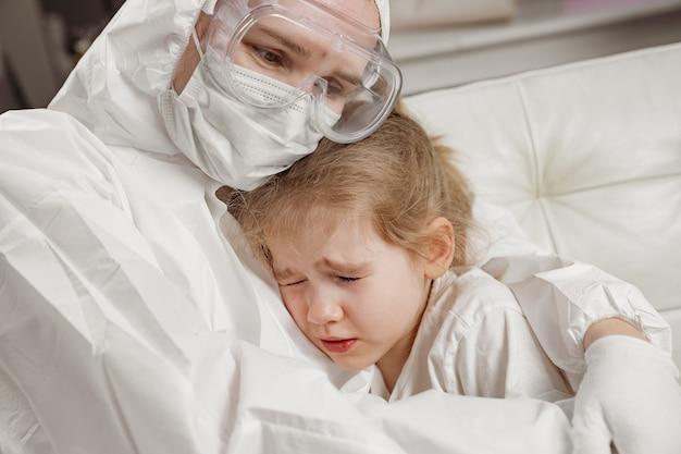 보호복, 마스크, 장갑을 낀 의사가 아픈 소녀를 안아준다