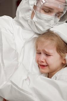 보호 복, 마스크, 장갑 및 안경을 쓴 의사는 진정되고 아픈 소녀를 안아줍니다.