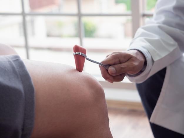 의사가 환자의 무릎을 검사 중입니다
