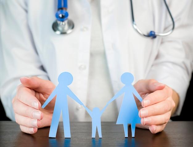 의사는 가족의 모습을 들고 있습니다. 가족 보호 개념.