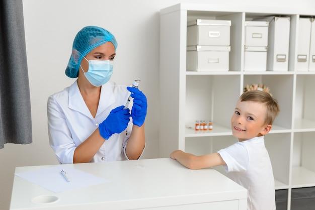 医者は男の子が振り返ったコロナウイルスに対して子供に予防接種をする準備をしています