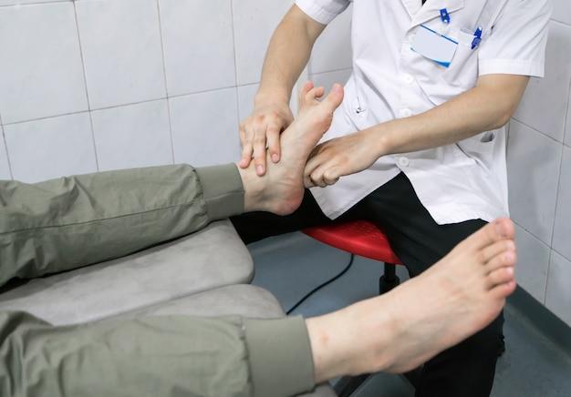 医者は患者の足を修復しています