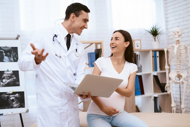 医者はラップトップに何かを見せています。
