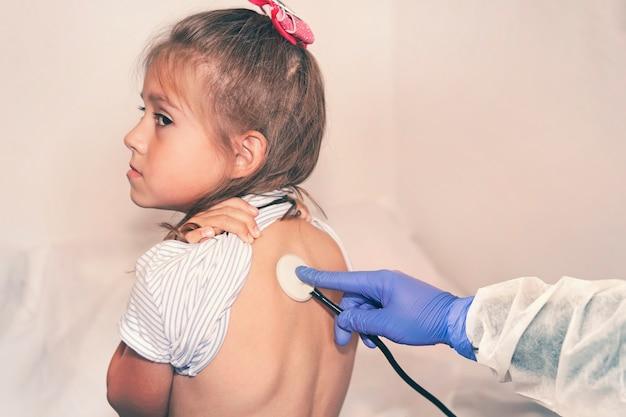 医者は病院で病気の女の子の肺に耳を傾けます。小児科医の予約の子供。病気の定義。子供の健康診断。