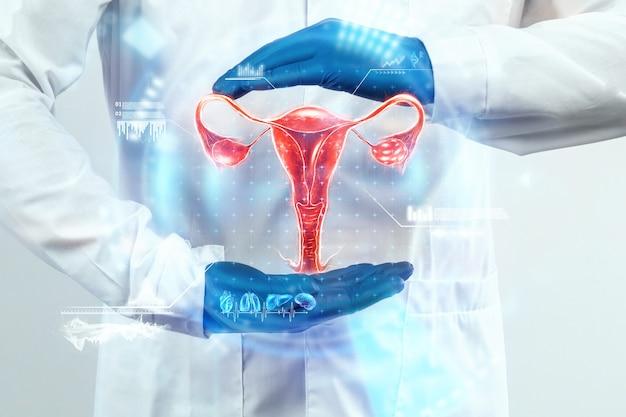 医師は女性の子宮のホログラムを見て、検査結果を確認します。卵巣疾患、子宮外妊娠、痛みを伴う期間、手術、革新的な技術、未来の薬。