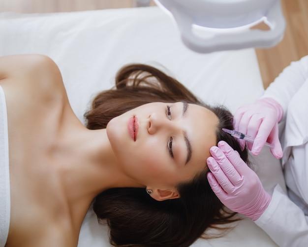 医者は髪の成長のために頭皮に注射をします